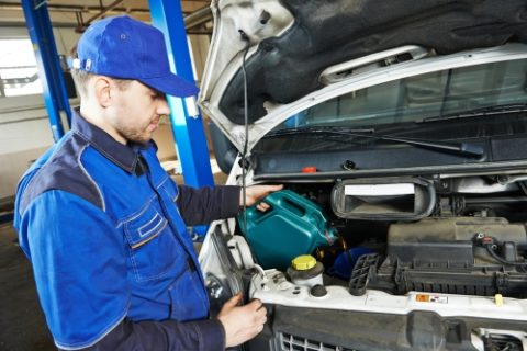 Technician Filling Car with Oil